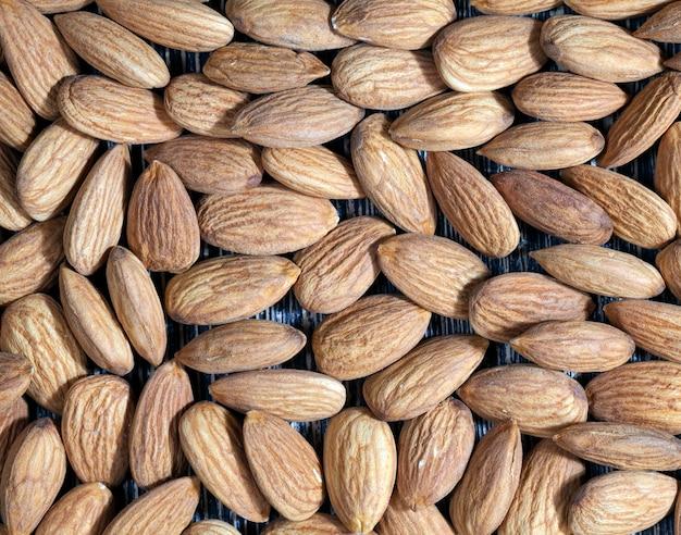 Hochwertige rohe nüsse, essfertig, mandeln auf dem küchentisch während des kochens, mandeln frisch und geschält, die oberfläche der nüsse ist nicht perfekt und weist aufgrund ihrer zubereitung in lebensmitteln einige natürliche mängel auf