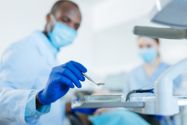 Hochwertiges instrument. der fokus liegt auf der hand eines angenehmen männlichen zahnarztes, der gummihandschuhe trägt und einen mundspiegel aus dem tablett nimmt