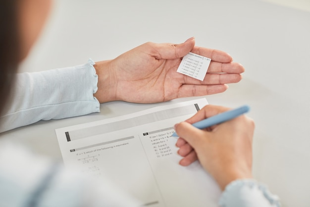 Hochwinkel-nahaufnahme eines nicht erkennbaren schülers, der während der prüfung in der schule eine cheat-notiz hält, platz kopieren