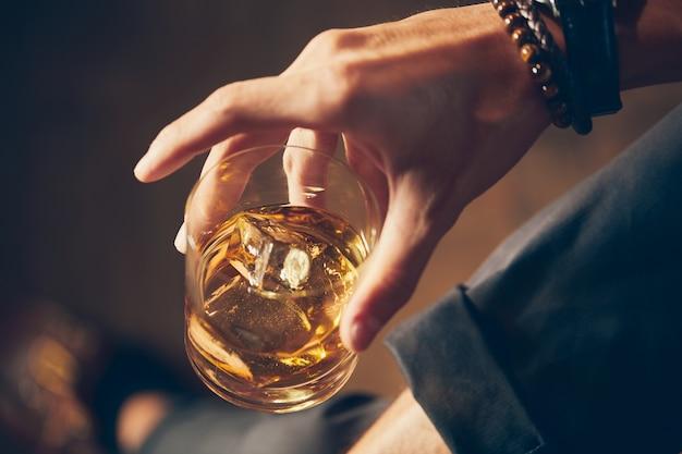 Hochwinkel-nahaufnahmeaufnahme eines mannes, der ein glas whisky hält