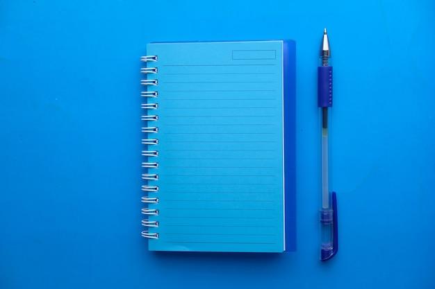 Hochwinkelansicht des offenen notizblocks auf blauem hintergrund