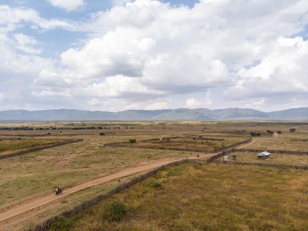 Hochwinkelaufnahme der bauernhöfe mit den bergen im hintergrund, die in samburu, kenia gefangen genommen werden
