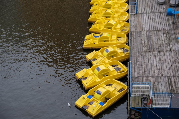 Hochwinkelaufnahme der gelben tretboote, die zum holzsteg auf der ruhigen wasseroberfläche müde sind