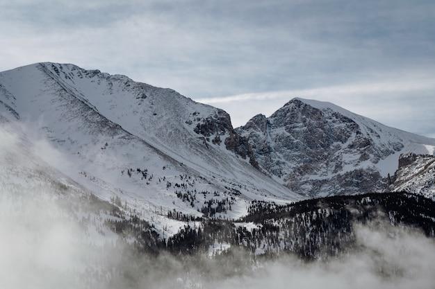 Hochwinkelaufnahme der mit schnee bedeckten berge unter dem bewölkten himmel