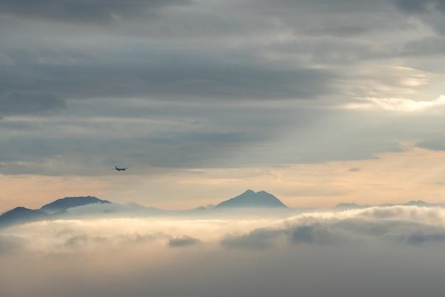 Hochwinkelaufnahme der schönen berggipfel, die durch die wolken und den nebel sichtbar sind