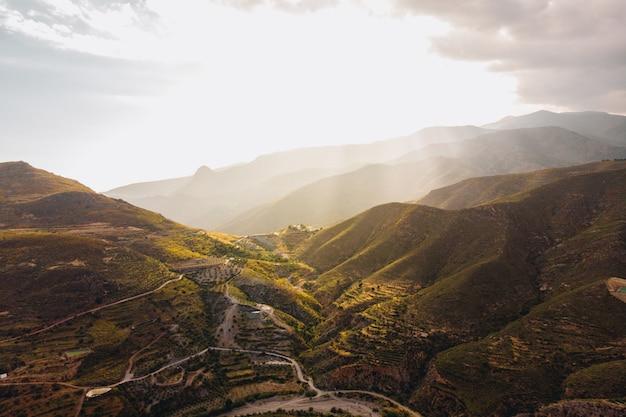 Hochwinkelaufnahme der schönen grünen berge unter dem sonnenlicht, das in andalusien, spanien gefangen genommen wird