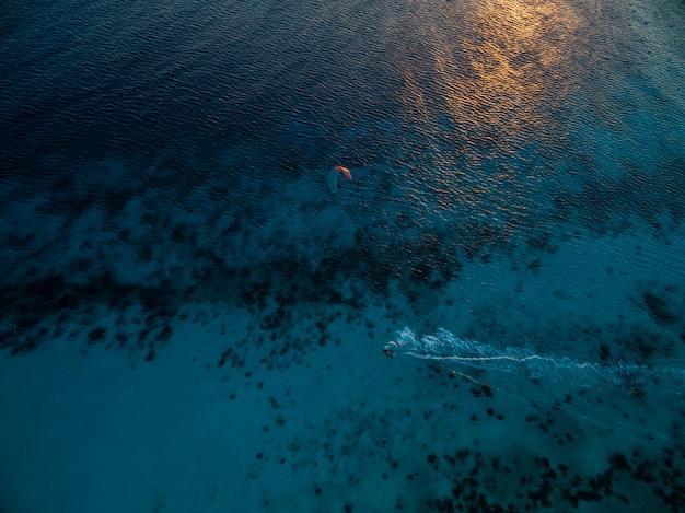 Hochwinkelaufnahme des ozeans beim kitesurfen. bonaire, karibik