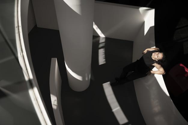 Hochwinkelaufnahme einer frau, die sich auf weiße wand in einem gebäude mit einem schwarzen boden stützt