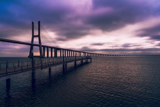 Hochwinkelaufnahme einer holzbrücke über dem meer unter dem purpurfarbenen himmel