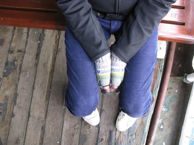 Hochwinkelaufnahme einer person, die auf einem holzstuhl sitzt und die hände zusammenhält