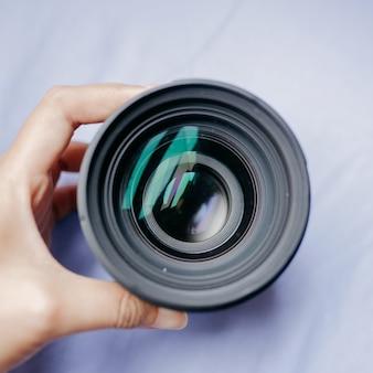 Hochwinkelaufnahme einer person, die ein kameraobjektiv hält
