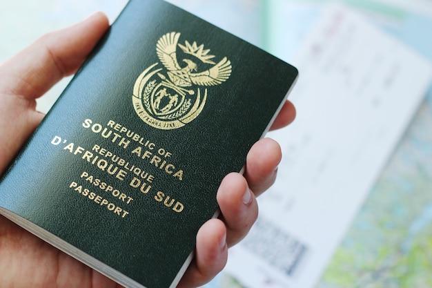 Hochwinkelaufnahme einer person, die einen pass über einem flugticket und einer geografischen karte hält