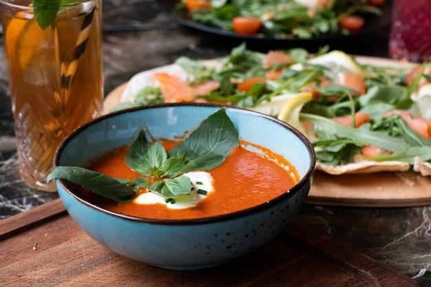Hochwinkelaufnahme einer schüssel tomatensuppe und eines tellers mit frischem salat auf einem tisch