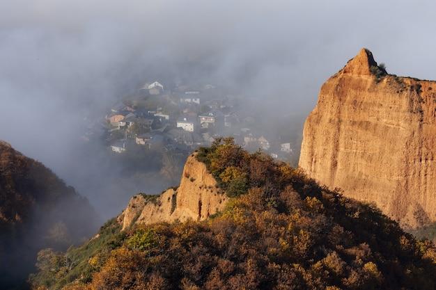 Hochwinkelaufnahme eines baumbewachsenen berges mit einem im nebel gefangenen dorf