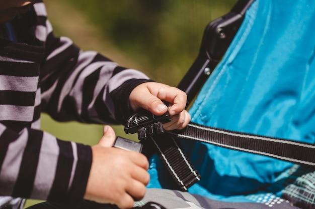 Hochwinkelaufnahme eines kindes, das seinen blauen autositz repariert, der an einem sonnigen tag gefangen genommen wird