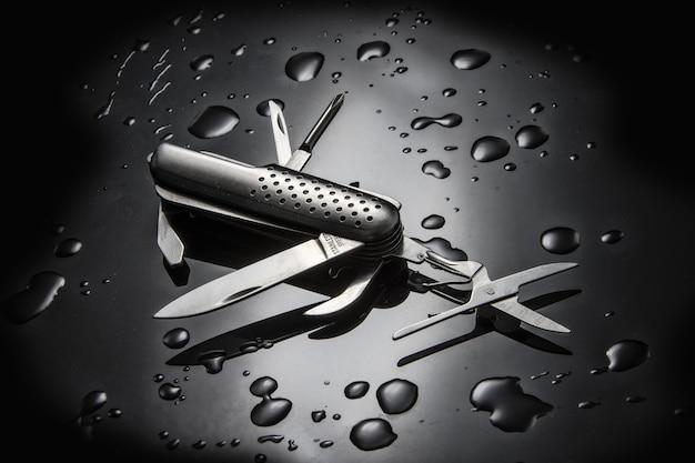 Hochwinkelaufnahme eines mehrzweckmessers aus metall mit wassertröpfchen isoliert auf schwarzer oberfläche