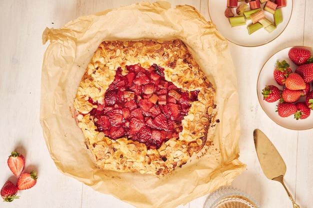 Hochwinkelaufnahme von köstlichem rhabarber-erdbeer-gallat-kuchen mit zutaten auf einem weißen tisch