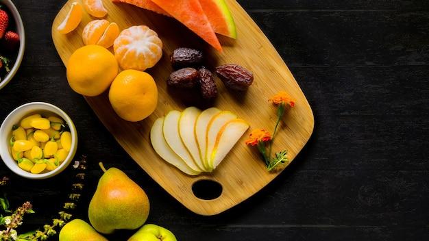Hochwinkelaufnahme von trauben, birnen, orange, wassermelone und datteln auf einem schneidebrett