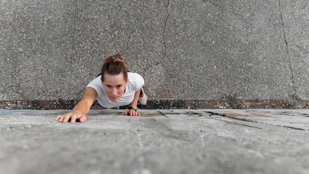 Hochwinkelfrau, die auf gebäuden klettert