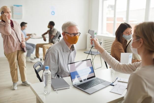 Hochwinkeliger blick auf einen älteren mann mit maske bei der sicherheitskontrolle im impfzentrum, kopierraum