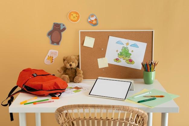 Hochwinkeliger kinderschreibtisch mit büchertasche und tablet