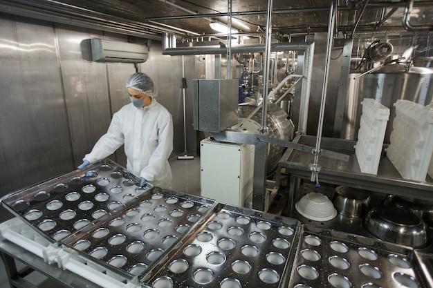 Hochwinkeliges hintergrundbild des industriellen förderbandes in einer sauberen lebensmittelproduktionsfabrik mit nicht erkennbarer arbeiterin, kopierraum