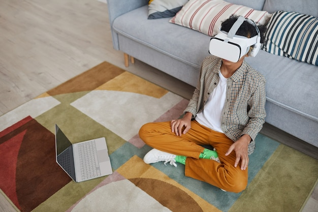 Hochwinkeliges porträt eines afroamerikanischen teenagers, der vr-ausrüstung trägt, während er videospiele spielt, die zu hause auf dem boden sitzen, kopierraum