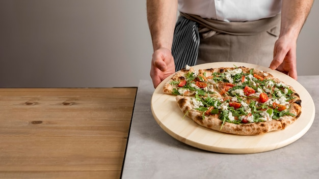 Hochwinkelmann, der schneidebrett mit frischer pizza hält