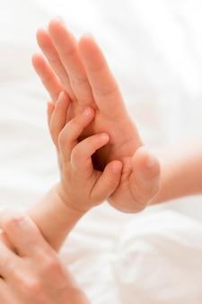 Hochwinkelmutter, die babys hand hält