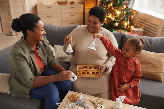 Hochwinkelporträt aller frauen afroamerikanischer familie, die haus für weihnachten zusammen verzieren