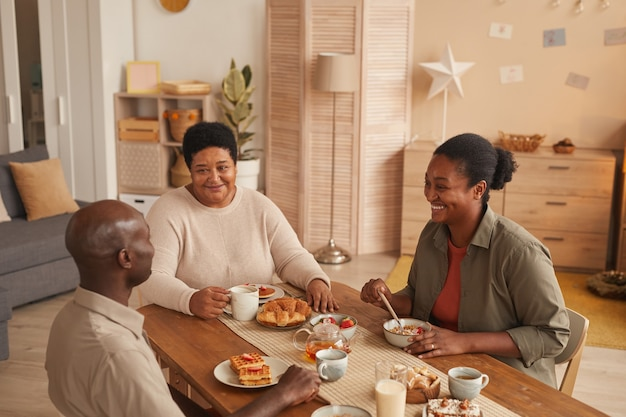 Hochwinkelporträt der glücklichen afroamerikanischen familie, die am esstisch sitzt, während das frühstück zu hause genießt