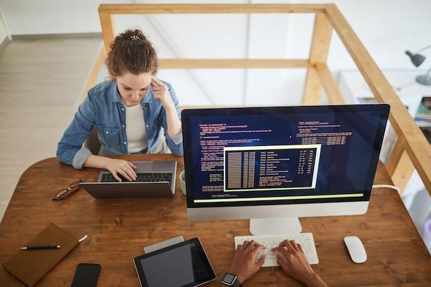 Hochwinkelporträt der jungen frau unter verwendung des laptops während der arbeit am schreibtisch in der softwareentwicklungsagentur mit nicht erkennbarem männlichen kollegen, der code auf computerbildschirm im vordergrund, kopierraum schreibt