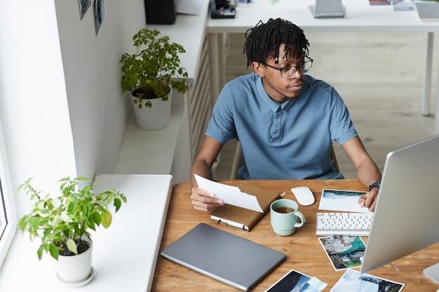 Hochwinkelporträt des kreativen afroamerikanischen mannes, der fotografien während der bearbeitung und veröffentlichung im modernen büro-, kopierraum überprüft