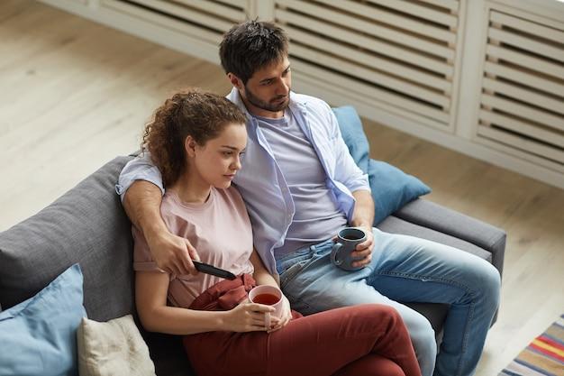 Hochwinkelporträt des modernen paares, das fernsieht und becher hält, während zu hause auf sofa in der gemütlichen wohnung sitzen und faule zeit genießen