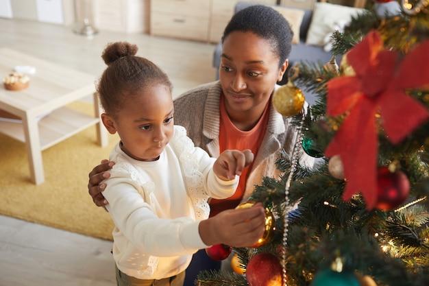 Hochwinkelporträt des niedlichen afroamerikanischen mädchens, das weihnachtsbaum mit lächelnder glücklicher mutter im gemütlichen innenraum verziert