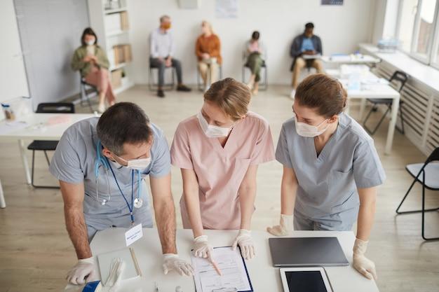 Hochwinkelporträt von drei ärzten, die masken tragen, die in der medizinischen klinik am schreibtisch stehen, kopierraum