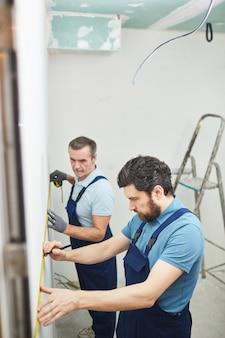 Hochwinkelporträt von zwei bauarbeitern, die wand beim renovieren des hauses messen, raum kopieren