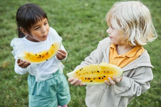 Hochwinkelporträt von zwei kleinen kindern, die draußen wassermelone essen und lächeln