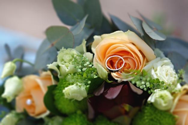 Hochzeit, blumenstrauß der braut mit goldenen ringen. dekoration für die feierliche zeremonie.