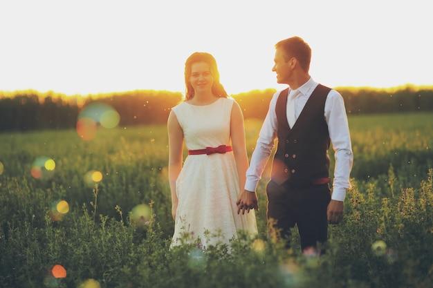 Hochzeit. braut und bräutigam halten sich an den händen und gehen im sonnenuntergangslicht im park spazieren