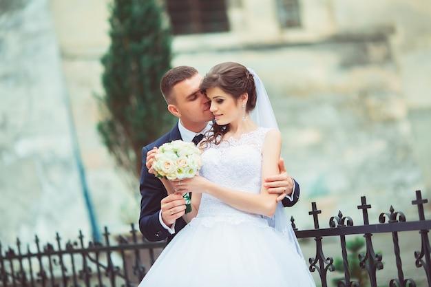 Hochzeit copule. schöne braut und bräutigam. frisch verheiratet. nahansicht. glückliche braut und bräutigam auf ihrer hochzeit umarmen. bräutigam und braut in einem park. hochzeitskleid. brauthochzeitsstrauß von blumen