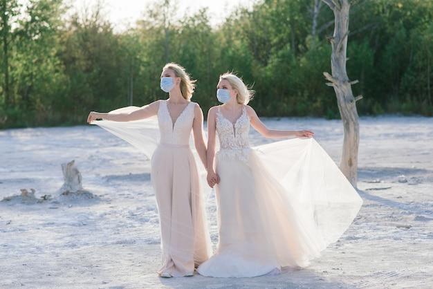 Hochzeit eines lesbischen paares auf weißem sand, masken tragen, um die epidemie covid-19 zu verhindern
