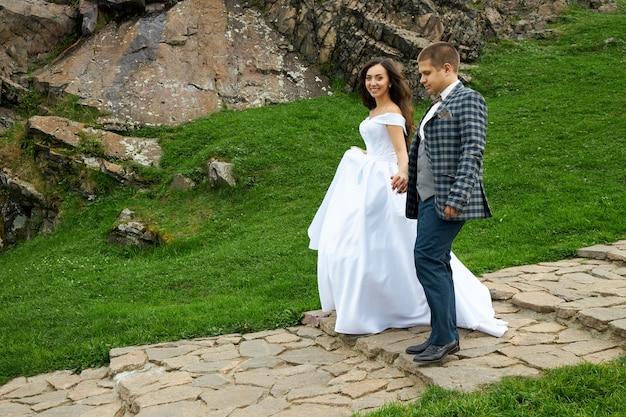 Hochzeit eines verliebten paares in der natur am leuchtturm. umarmungen und küsse von braut und bräutigam