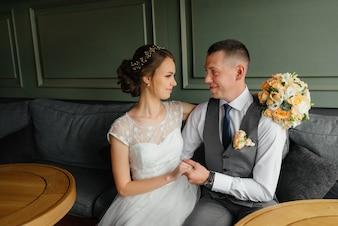 Hochzeit. Hochzeitstag. Schöne Braut und eleganter Bräutigam betrachten einander im Innenraum.