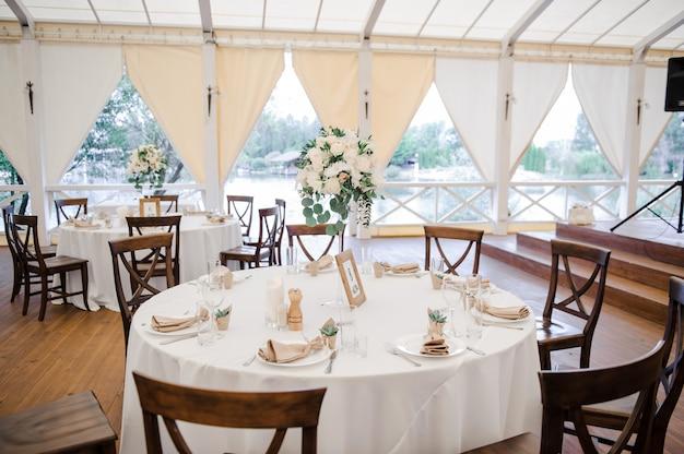 Hochzeit im zelt. dekoration der halle. weiße tischdecken, schönes dekor und geschirr.