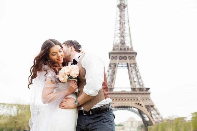 Hochzeit in paris. glückliches gerade verheiratetes paar, das nahe dem eiffelturm umarmt