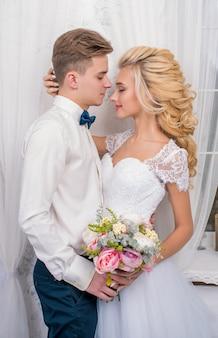 Hochzeit mit dekorküssen, umarmungen. glückliches paar. liebt braut und bräutigam in luxusdekoration. braut und bräutigam zusammen. paar umarmt. jungvermählten am hochzeitstag