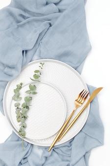 Hochzeit oder festliche tischdekoration. teller und besteck mit grauem dekorativem textil auf weißem hintergrund. schöne anordnung.
