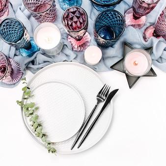 Hochzeit oder festliche tischdekoration. teller, weingläser, kerzen und besteck mit grauem dekorativem textil auf weißem hintergrund. schöne anordnung.