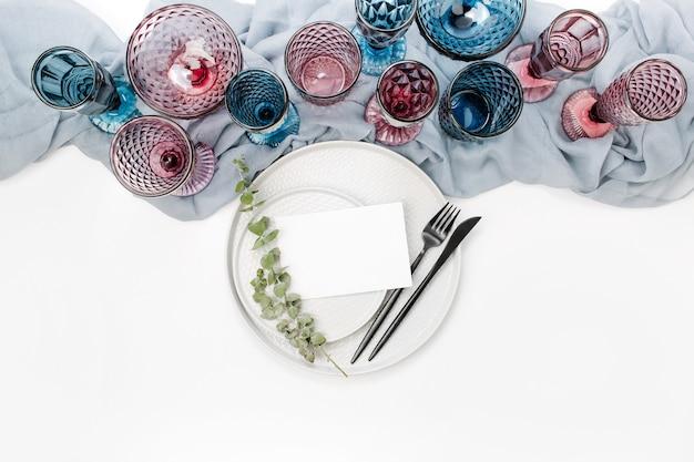 Hochzeit oder festliche tischdekoration. teller, weingläser und besteck mit grauem dekorativem textil auf weißem hintergrund. schöne anordnung.